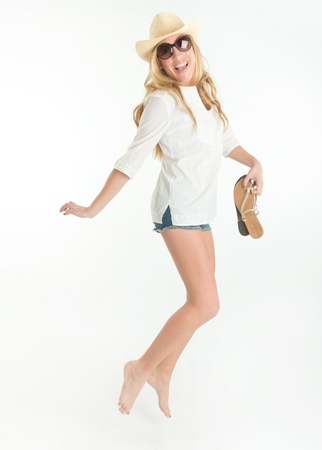 barefoot cowboy: Happy woman in shorts, jumping while holding her shoes