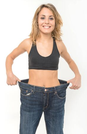 big women: Successful weight loss, woman with too large jeans after a diet