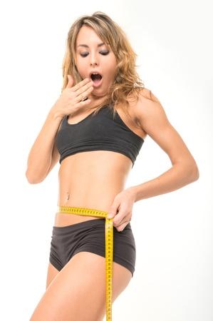 astonished slim woman measuring her waist photo