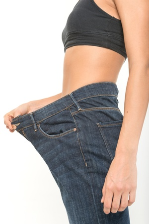 weight loss woman: Successful weight loss, woman with too large jeans after a diet