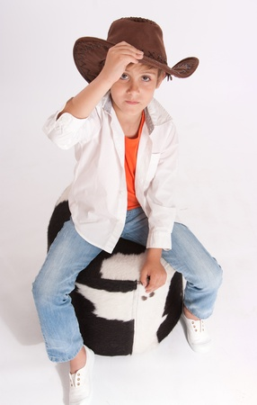 cowhide:   Kid with a cowboy hat riding a cowhide footstool