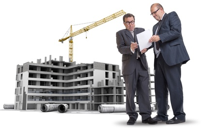 duress: Two men in a dubious business deal by a building under construction Stock Photo