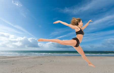 exotic woman: Young woman flying in a graceful jump at the beach  Stock Photo