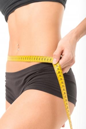 woman measuring waist: Woman measuring her thin waist