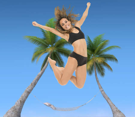 Young woman jumping with a hammock tied to two palm trees and a blue sky in the background photo