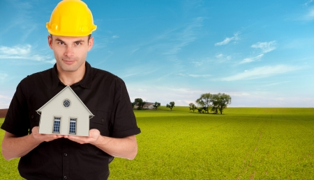 prefabricated building: An architect in a field holding a house on his hands
