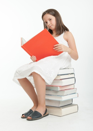 Young girl sitting on a pile of books and reading one Stock Photo - 19171686