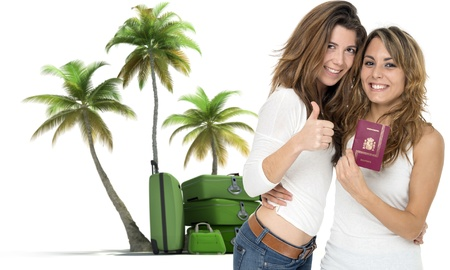 Two happy female friends holding a passport, with a pile of luggage and palmtrees at the background photo