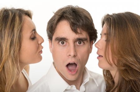 rumor: Two girls whispering in the ears of a young man with a shocked expression