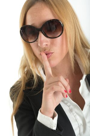hushing: Woman with sunglasses doing a hushing gesture Stock Photo