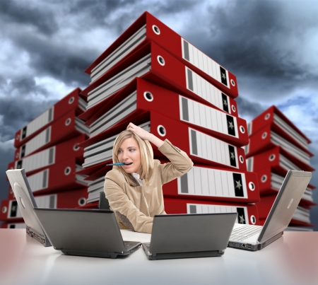 filing documents: Stressed young woman using multiple computers, with piles of folders on the backgrounds