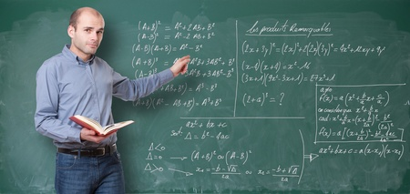 high school teacher: Young man by a chalkboard with formulae