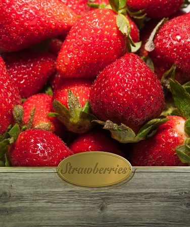 Fresh strawberries framed in wood with a golden label photo