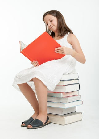 Young girl sitting on a pile of books and reading one Stock Photo - 19606927