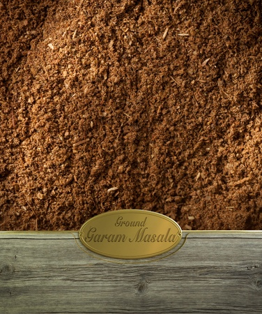 Ground Garam masala spices frame in wood with a golden label photo