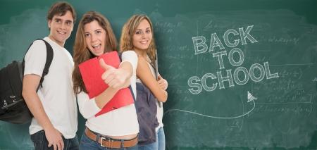 school backpack: Felices los jóvenes de una pizarra con las palabras de regreso a la escuela