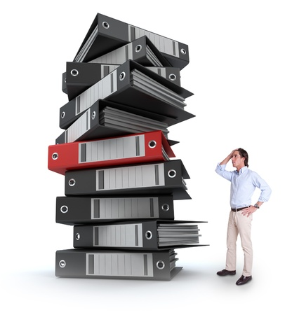 filing documents: Stressed man overwhelmed by a huge pile of files