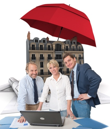 sheltered: Business team and a house with blueprints  sheltered under an umbrella Stock Photo