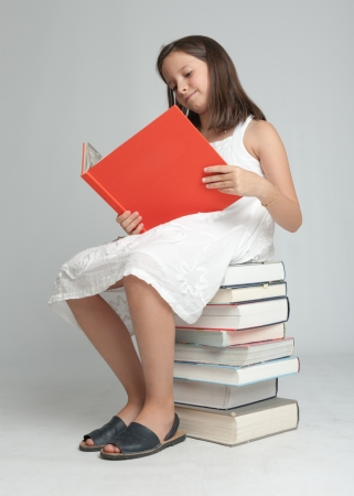 Young girl sitting on a pile of books and reading one Stock Photo - 20276197