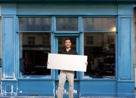 window opening: Man standing with a blank sign by a store