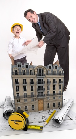 Father and son with blueprints and a building photo