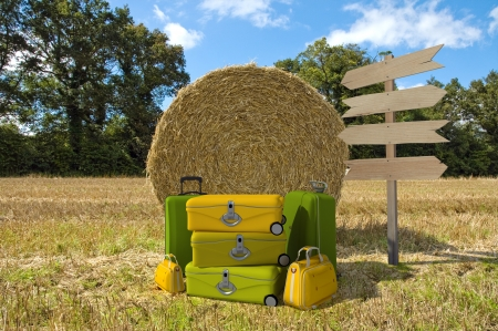 A pile of luggage with directional signs pointing everywhere in the middle of a field with hay bales photo