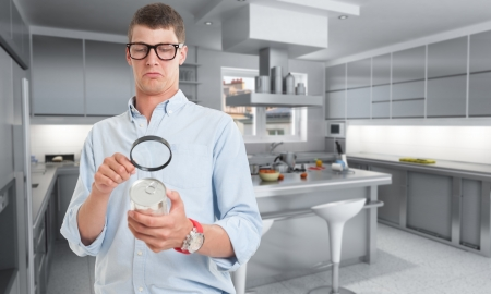 inspect: Young man examining a can through a magnifying glass in a kitchen