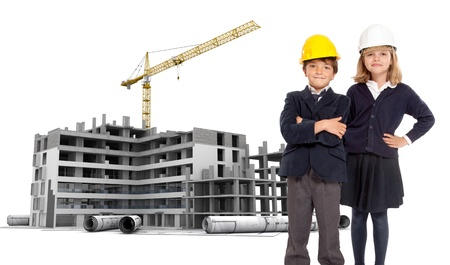 Young kids in school uniform with safety helmets by a building under construction photo