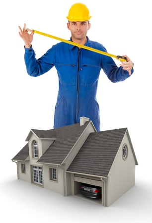 Professional worker extending a tape measure by a model house Stock Photo