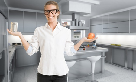Young woman in a kitchen holding an apple with one hand and a can in the other photo