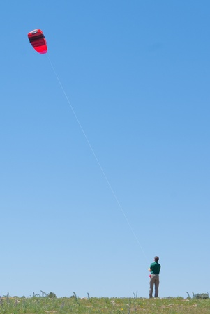 flying man: Man flying a kite in a sunny day Stock Photo