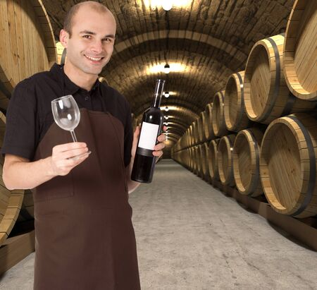 winemaking: Young man holding a wine bottle and a wineglass in a cellar Stock Photo