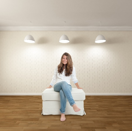Happy young woman sitting barefoot in a minimalist apartment photo