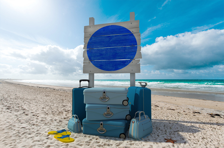 Pile of luggage and wooden sign in a tropical beach photo