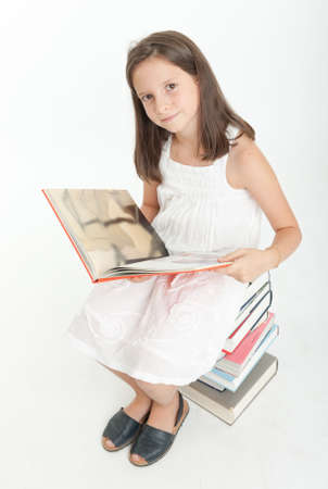 Young girl sitting on a pile of books and reading one Stock Photo - 22260868