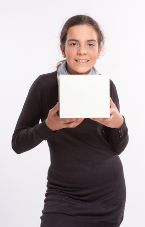 early teens: Girl in her early teens holding a blank box Stock Photo