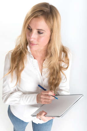 taking inventory: Portrait of an attractive young blonde writing on a notebook