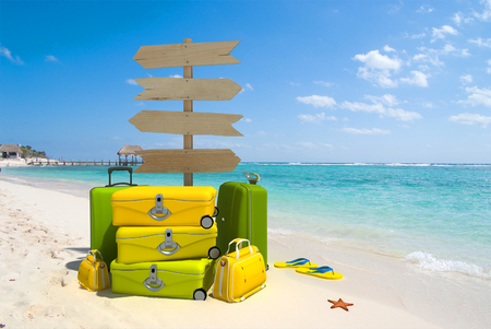 A wooden sign post , a pile of luggage, thongs and starfish on a beach resort photo