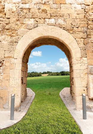 archway: Archway in a fortification leading to a green fields