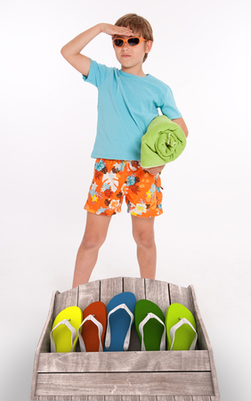 beach wear: Young boy in beach wear and a group of colorful flip-flops