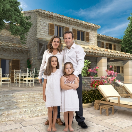 Happy family standing by a beautiful villa with swimming pool photo