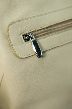 zipped: Detail of a zipped pocket on a white leather handbag Stock Photo