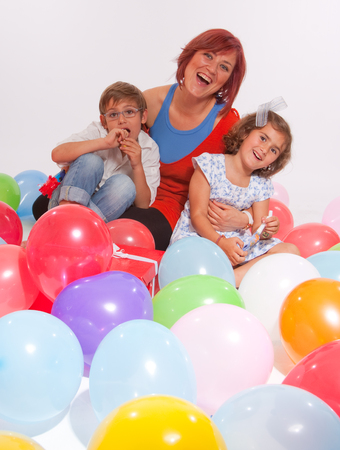 Mother and kids playing with colourful balloons    photo