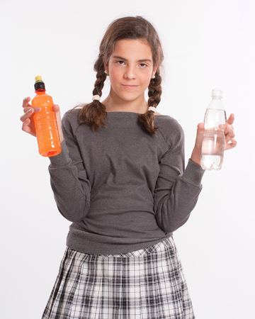 A girl holding a bottle in each hand, one with water, the other a bright orange beverage  photo