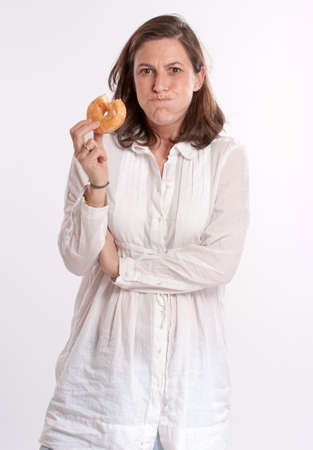 Woman eating a donut swelling her cheeks pretending to be getting fatter