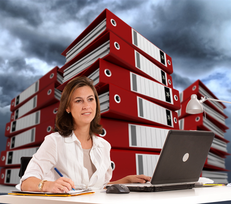 Woman sitting at her desk with piles of ring binders at the background and a cloudy sky photo