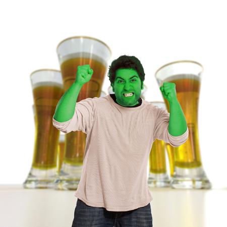 amok: Zielony młody człowiek w przypływie wściekłości z piwa na tle Zdjęcie Seryjne