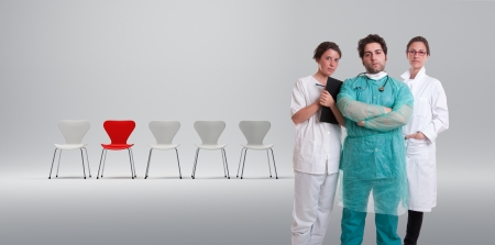 A surgeon and his team with a row of white chairs and a red one photo