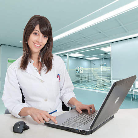 admissions:  Young female hospital administrative in a desk at the hospital hall  Stock Photo