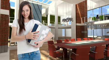 Casual attractive brunette carrying some books in a beautiful modern office in a loft   photo